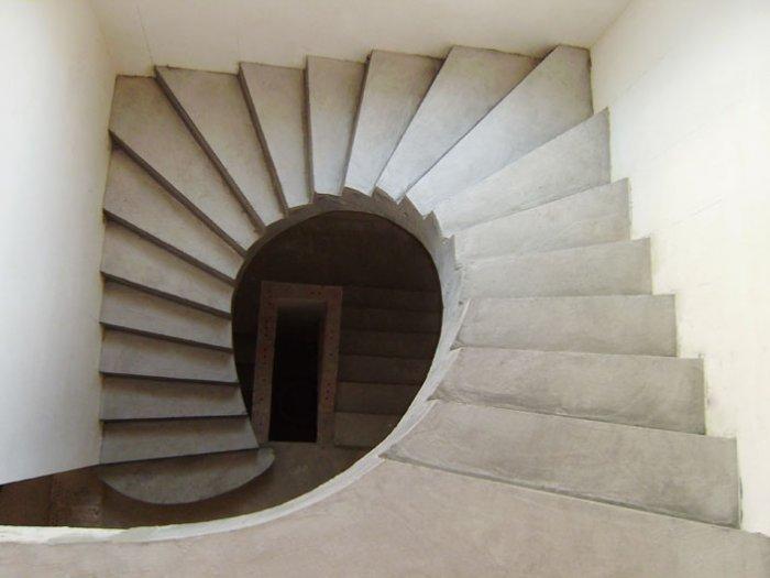 Бетонная лестница винтового вида в трехэтажном доме